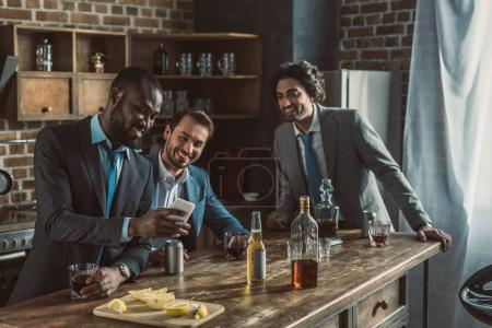 smiling male friends in suits using smartphone and drinking alcohol beverages while partying at home