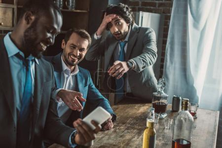 emotional man looking at laughing friends using his smartphone during party