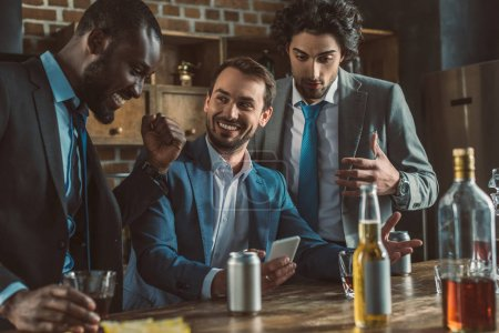 cheerful multiethnic men in suits using smartphone and drinking alcoholic beverages together