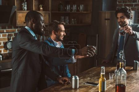 happy multiethnic men drinking whisky and partying together