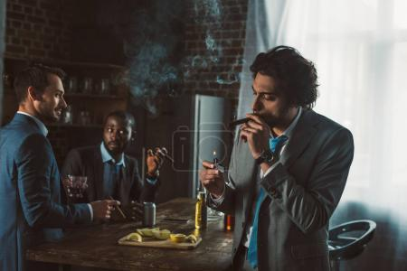 handsome young businessman smoking cigar while friends drinking whiskey behind