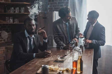 three multiethnic men in suits drinking alcohol beverages and smoking cigars together