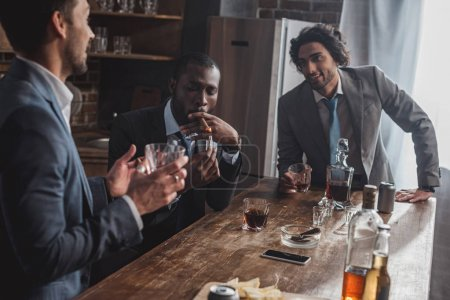 cropped shot of smiling multiethnic businessmen talking while smoking cigars and drinking whiskey