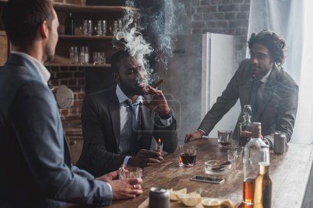 young multiethnic businessmen talking while smoking cigars and drinking whiskey
