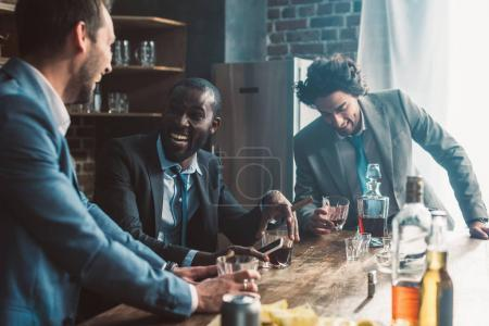 cheerful male friends laughing and drinking whiskey together