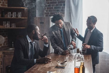 male friends talking while drinking alcohol and smoking cigars