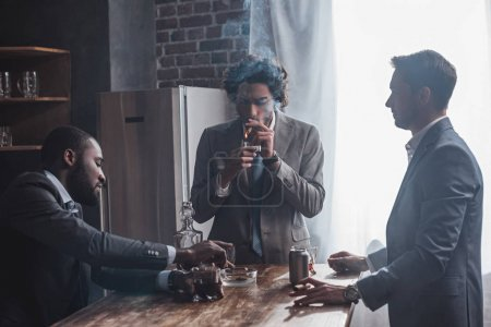 Photo for Young multiethnic businessmen smoking cigars and drinking alcohol together - Royalty Free Image
