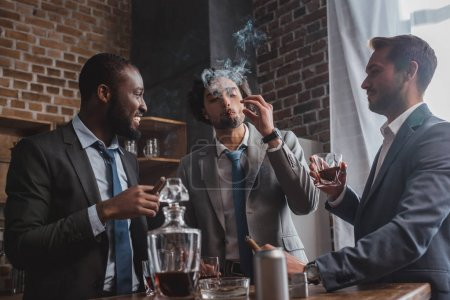 multiethnic male friends in suits smoking cigars, drinking whiskey and talking
