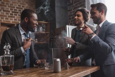 smiling multiethnic male friends in suits smoking cigars, drinking whiskey and talking