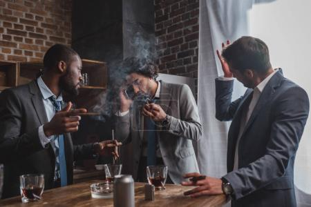 emotional young businessman smoking cigar and talking by smartphone while friends drinking whiskey