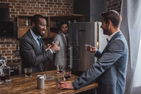 smiling multiethnic businessmen looking at each other and friend hiding behind refrigerator while partying together