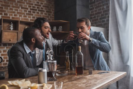 Photo for Cheerful multiethnic men looking at friend drinking alcoholic beverages from glass and can - Royalty Free Image