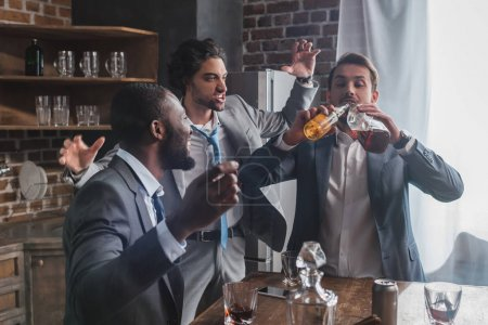 excited multiethnic men looking at friend drinking alcoholic beverages from bottles
