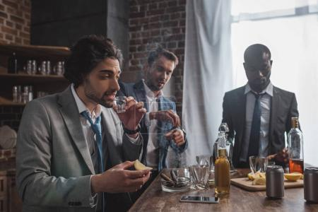 multiethnic male friends in formal wear drinking tequila and smoking cigars