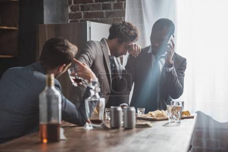 multiethnic men in suits drinking alcohol and talking by smartphone