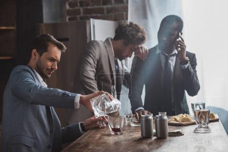 drunk multiethnic businessmen drinking whiskey together