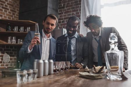 young multiethnic businessmen drinking alcohol beverages together