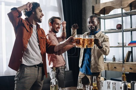 excited male friends clinking beer glasses while partying together