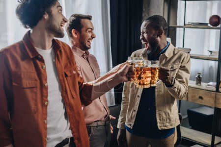 cheerful multiethnic male friends clinking beer glasses while partying together