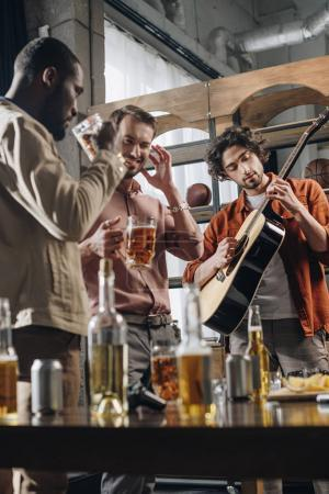 Photo for Happy young multiethnic friends drinking beer and playing guitar together - Royalty Free Image