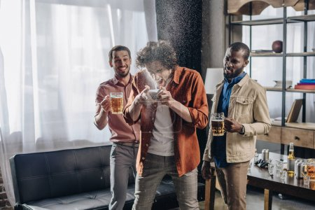 laughing multiethnic friends looking at man drinking beer from can