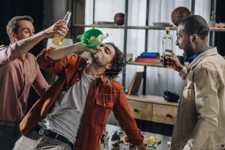 drunk male friends drinking alcohol beverages from funnel at party