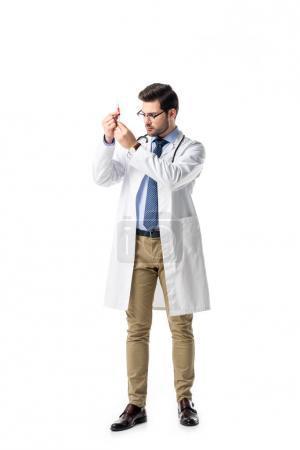 Doctor holding syringe wearing white coat with stethoscope isolated on white