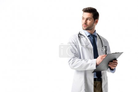 Thoughtful male medical worker wearing white coat with stethoscope and writing in clipboard isolated on white