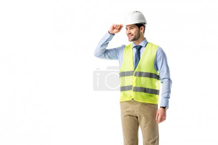 Smiling builder in reflective vest wearing helmet isolated on white