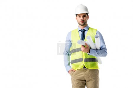 Handsome architect in reflective vest and helmet holding blueprints isolated on white