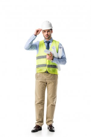 Young man in reflective vest and hard hat holding blueprints isolated on white