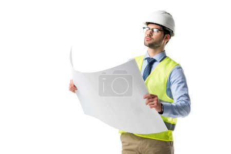 Photo for Confident architect in glasses wearing reflective vest and hardhat looking at blueprint isolated on white - Royalty Free Image