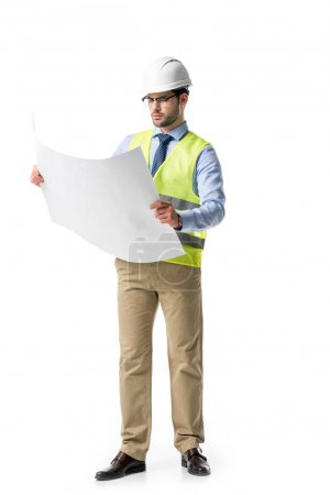 Thoughtful builder in reflective vest and helmet looking at blueprint isolated on white