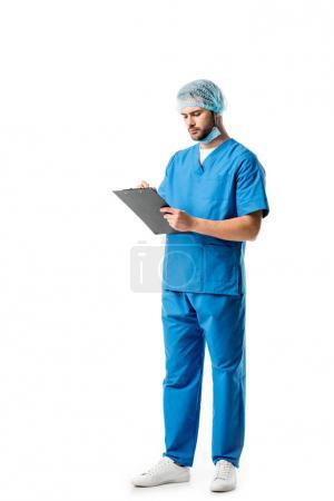 Thoughtful medical worker wearing blue uniform and writing in clipboard isolated on white