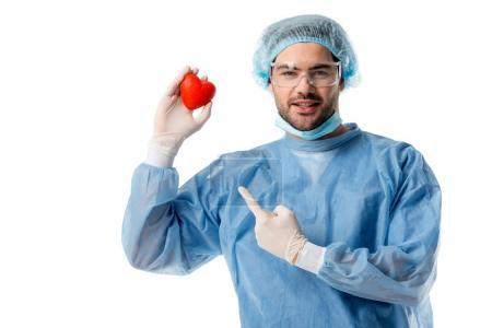 Smiling surgeon in blue medical uniform and medical mask and pointing at toy heart isolated on white