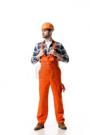 Confident handyman in orange overall and helmet isolated on white