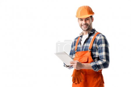 Smiling builder in orange overall and hard hat using digital tablet isolated on white
