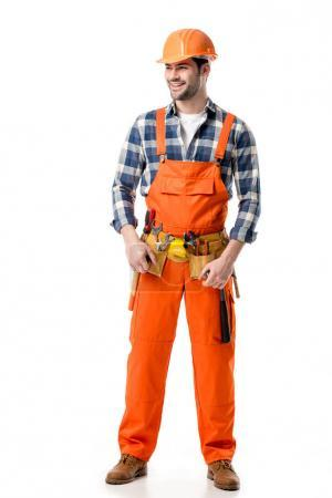Smiling builder in orange overall and tool belt isolated on white