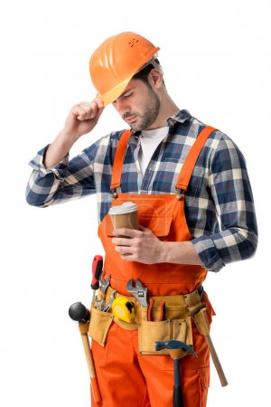 Repairman in orange overall and helmet holding coffee cup isolated on white