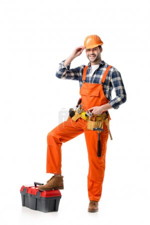 Smiling handyman in orange overall and hard hat leaning on tool box isolated on white