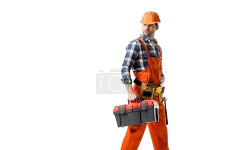 Photo pour Jeune constructeur en orange ensemble et casque dur portant boîte à outils isolé sur blanc - image libre de droit