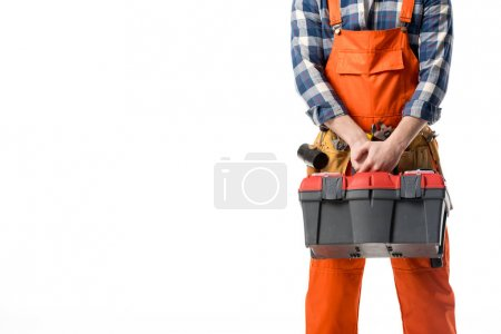 Cropped view of workman in orange overall holding tool box isolated on white