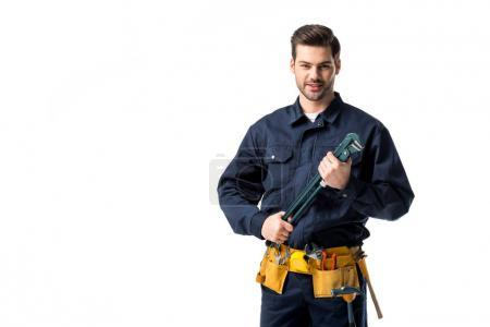 Smiling repairman wearing uniform with tool belt and holding wrench isolated on white