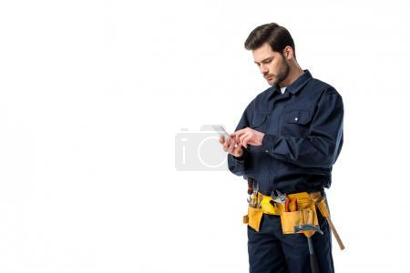 Professional plumber with tool belt using smartphone isolated on white