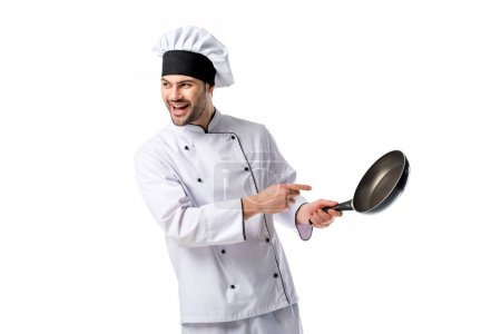 smiling chef in uniform pointing at frying pan in hand isolated on white