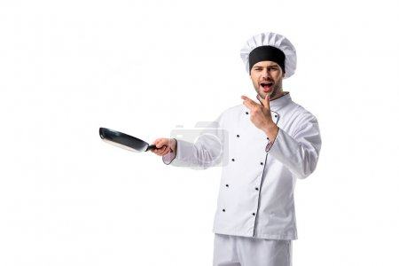 Photo for Portrait of emotional young chef in uniform with frying pan isolated on white - Royalty Free Image