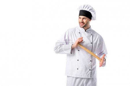 chef souriant en uniforme avec le rouleau à pâtisserie en bois isolé sur blanc