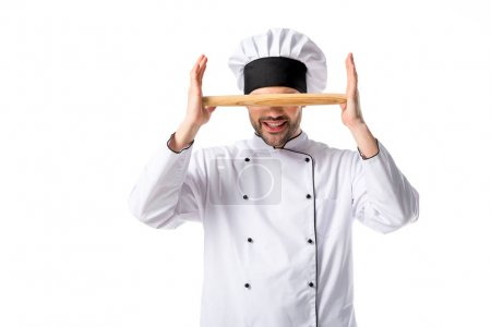 obscured view of chef in uniform with wooden rolling pin isolated on white
