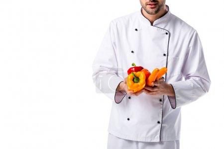 Photo for Partial view of chef in uniform with fresh vegetables in hands isolated on white - Royalty Free Image