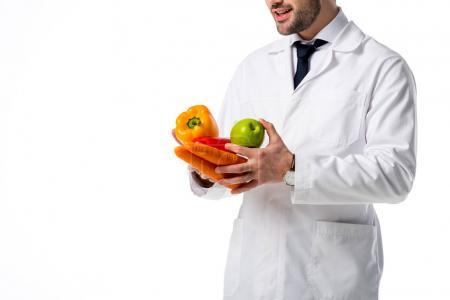 cropped shot of nutritionist in white coat with fresh vegetables and apple in hands isolated on white